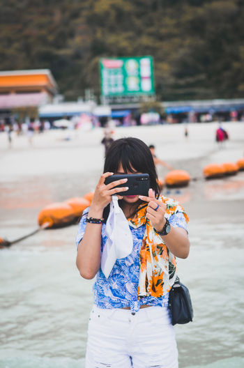 Woman photographing through smart phone while standing at beach