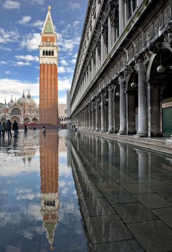 Reflection of tower on puddle in piazza san marco against sky