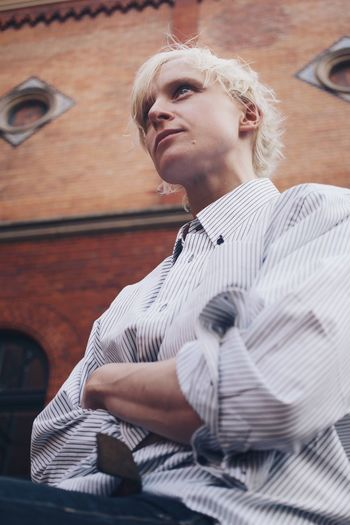 Low angle view of young woman looking away while sitting against wall