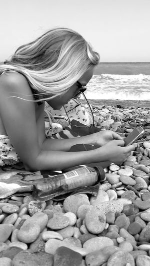 Woman sitting on pebbles at beach