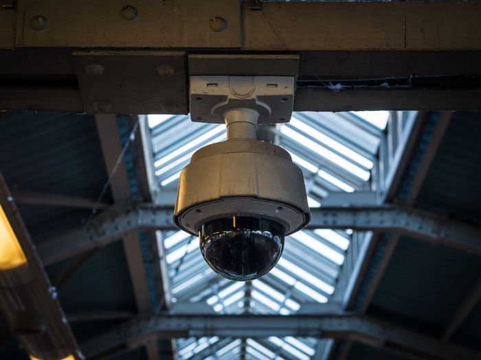 Low Angle View Of Security Camera Hanging On Ceiling In Train Station