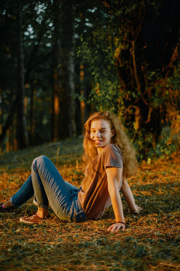 Full length of smiling young woman in forest