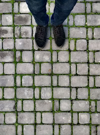 Low section of man standing on cobblestone footpath