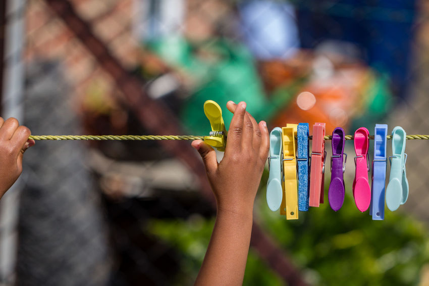 Child Girl Human Hand Focus On Foreground People One Person Outdoors Hanging Rope String Pegs Clothes Pegs Colorful Colourful Garden Afro Caribbean African American African Person Of Color Person Of Colour Peg Clothes Peg Washing Line