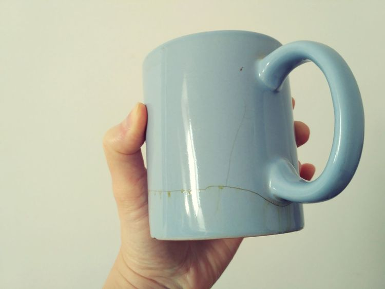Cracked blue mug in hand still with the bottom, luckily. Crack Cracked Mug Human Hand Human Body Part Studio Shot Drink Leak Leaking Dirty