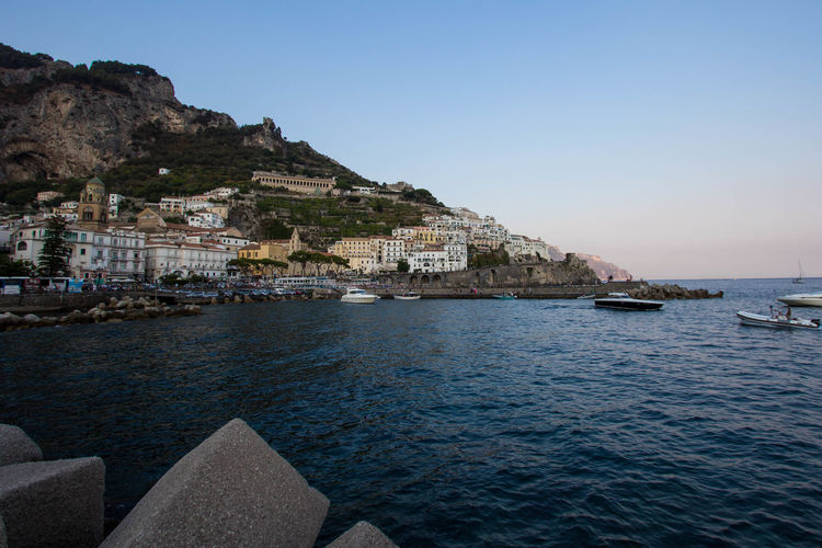 Scenic view of sea and townscape against clear sky