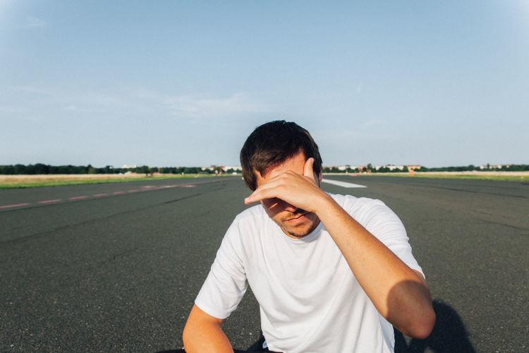 Man shielding eyes on road against sky