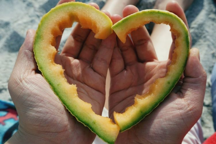 Close-up of person with heart shape muskmelon peel at beach