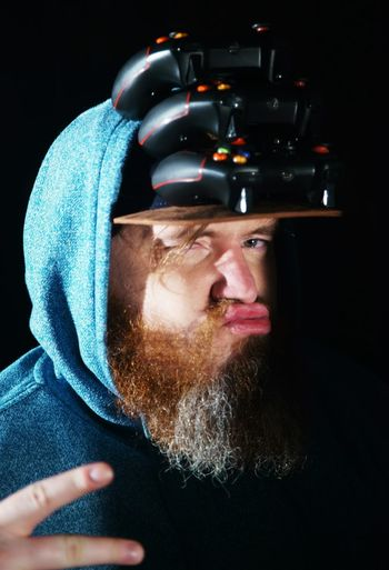 Portrait Of Bearded Man With Stacked Game Controllers On Cap Against Black Background