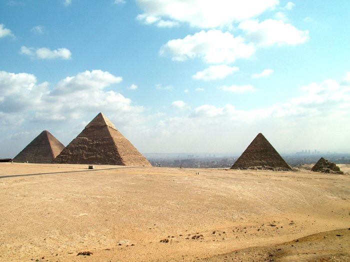 Pyramids at desert against sky during sunny day