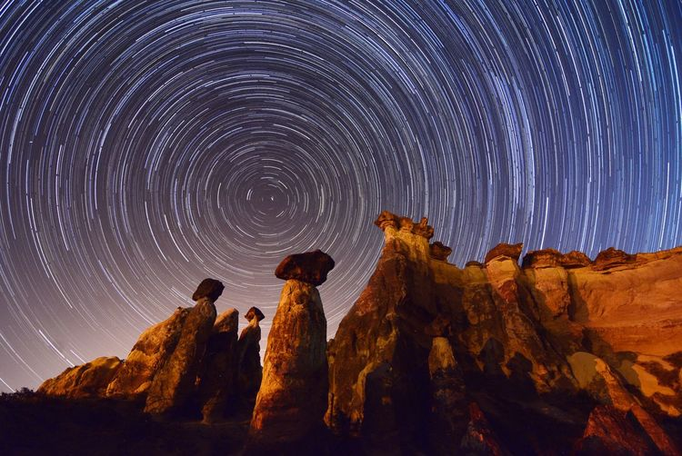 Low angle view of rock formations against star trail
