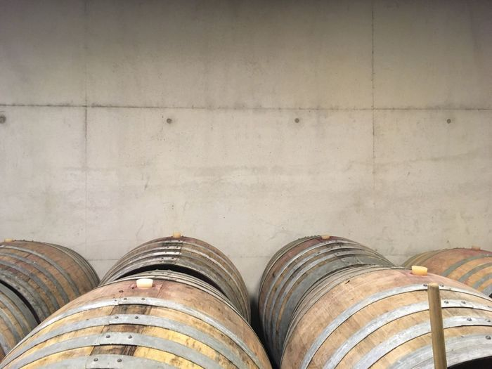 Barrels by wall in wine cellar