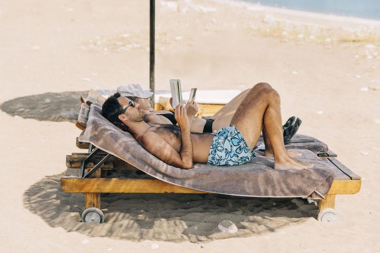 Full length of shirtless man relaxing at beach
