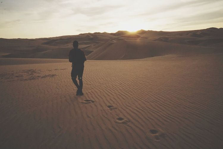 Rear view of man walking on desert against sky during sunset