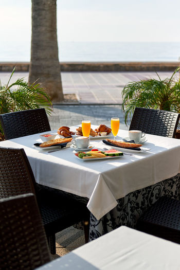 Outdoors restaurant. Table setting with classic breakfast. Orange juice, fruits and pastries Beverage Breakfast Morning Outdoors Restaurant Palm Tree Table Setting Chair Coffee Cup Croissant Cup Of Coffee Drink Food Food And Drink Glass Hotel No People Orange Juice  Outdoors Pastry Restaurant Seat Setting Table Table And Chairs Toast Bread