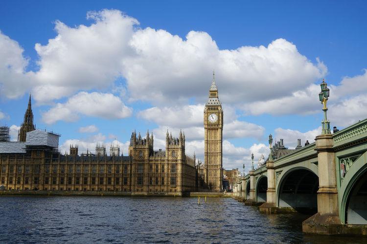 Westminster bridge over thames river by big ben against sky