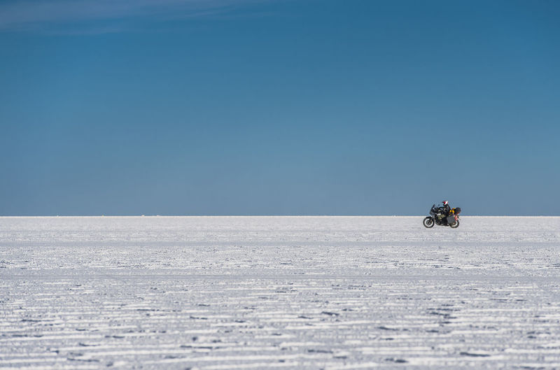 Man riding motorcycle on land against clear sky