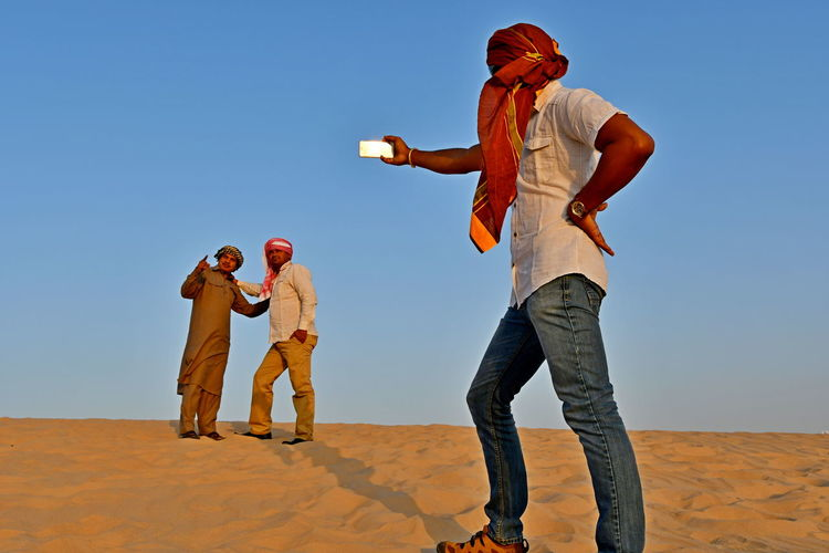 Man taking selfie while friends standing on desert against sky