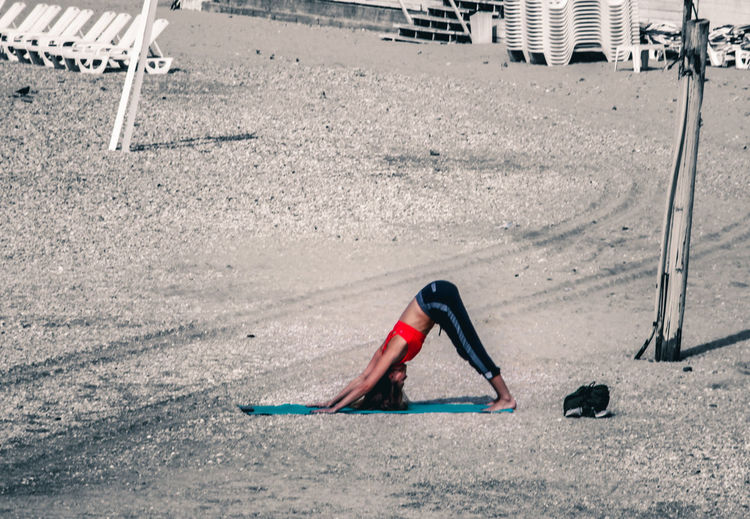 Close-up of woman practising yoga on beach