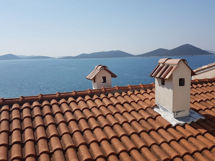 Air ducts on house roof by sea against clear sky