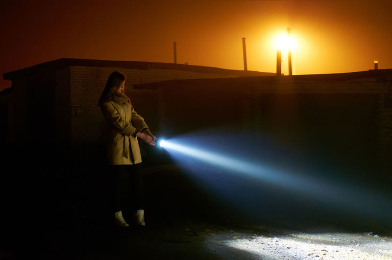 Side view of young woman holding flashlight while standing on road against orange sky during sunset