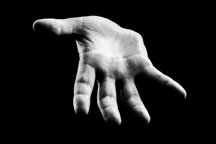 Cropped image of human hand against black background