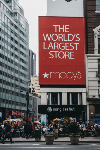People walking on a street in from of Macy's in Manhattan, New York, the world's largest department store. Tourism Travel United States USA New York City New York Macy's Manhattan Department Store Mall Shopping Advertisement Consumerism America NYC Real People City Life Sign Banner Building Text Building Exterior City Macys Retail