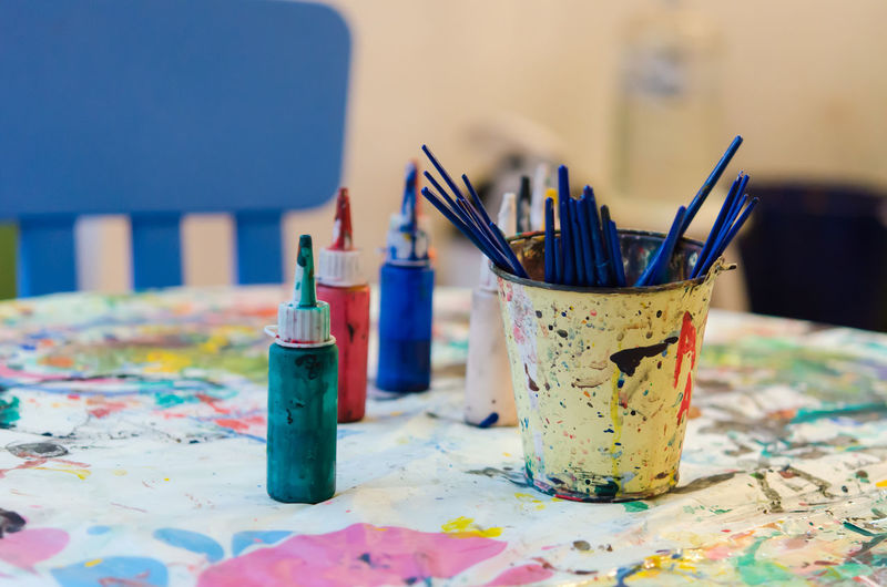 Paint brushes and water colors on messy table