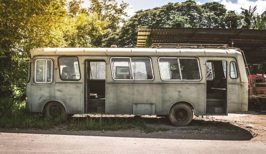Abandoned vintage van against trees
