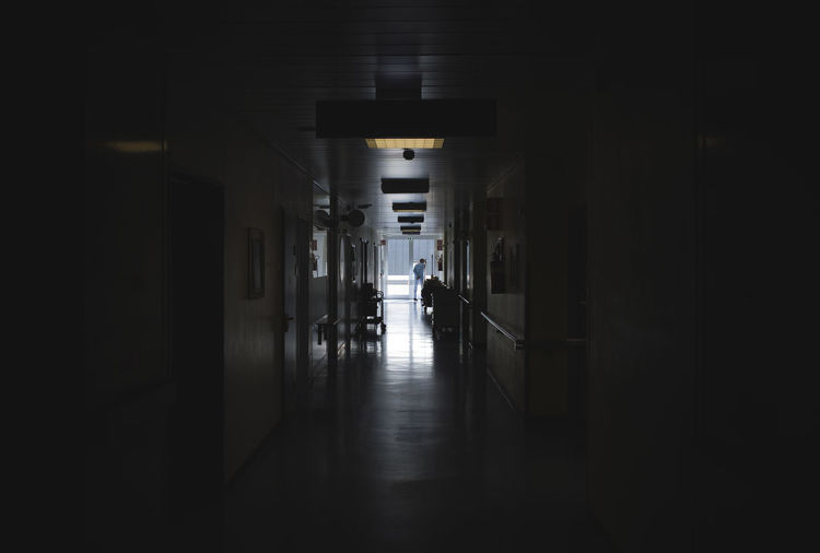 Man Standing In Corridor At Hospital