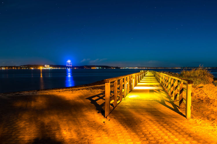 Pier over sea against clear sky at night