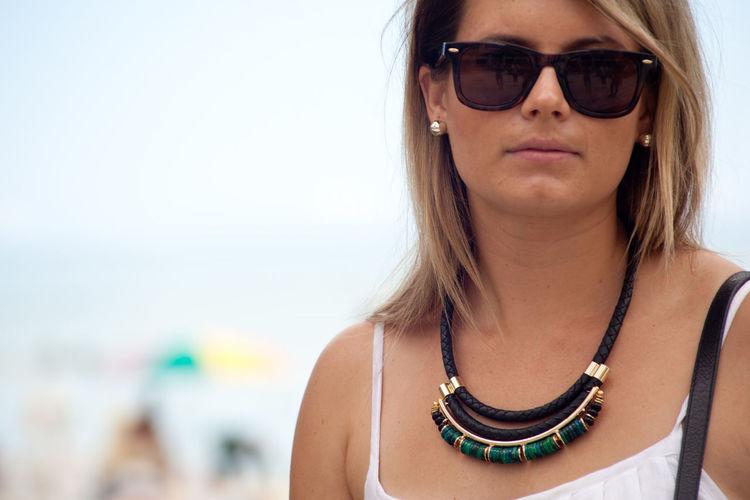 Close-up of woman wearing sunglasses on beach