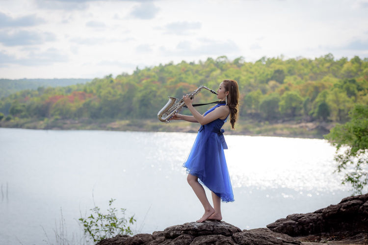 Beautiful woman wear blue evening dress sound saxophone stand on the rocks over mountains and rivers background. Adult Beautiful Woman Day Dress Fashion Focus On Foreground Full Length Hairstyle Holding Leisure Activity Lifestyles Nature One Person Outdoors Real People Side View Standing Water Women Young Adult Young Women