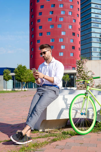 Young man using phone while sitting on bicycle in city