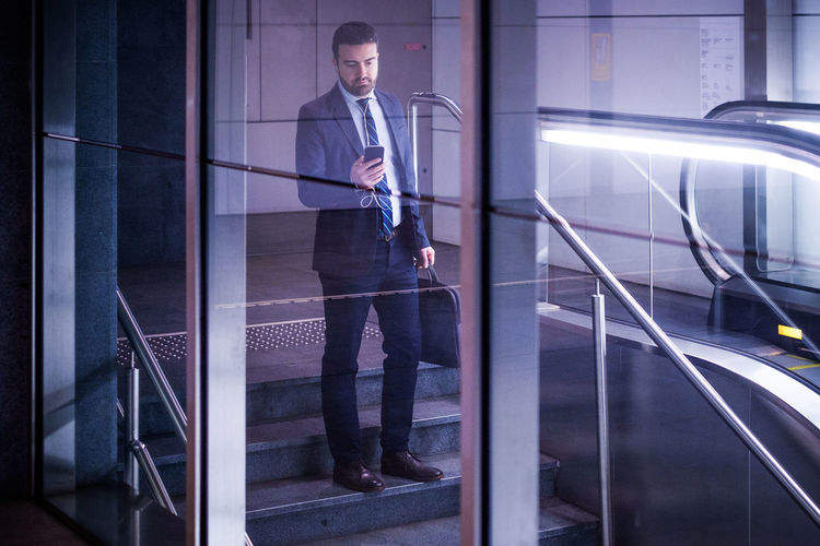 Architecture Business Person Businessman Contemplation Formalwear Full Length Glass - Material Indoors  Looking Males  Men One Person Railing Real People Standing Technology Well-dressed Young Adult Young Men