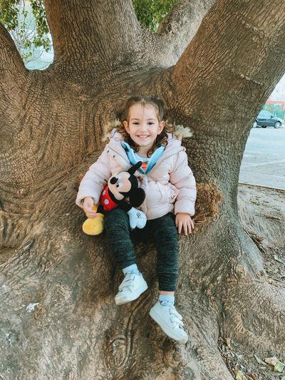 Full length of cute baby boy on tree trunk