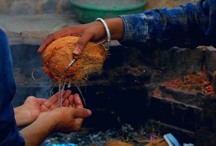 Cropped image of hand holding coconut at temple