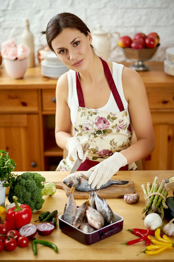 Portrait of smiling young woman preparing food at kitchen