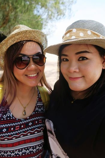 Close-up portrait of smiling friends wearing hats standing outdoors