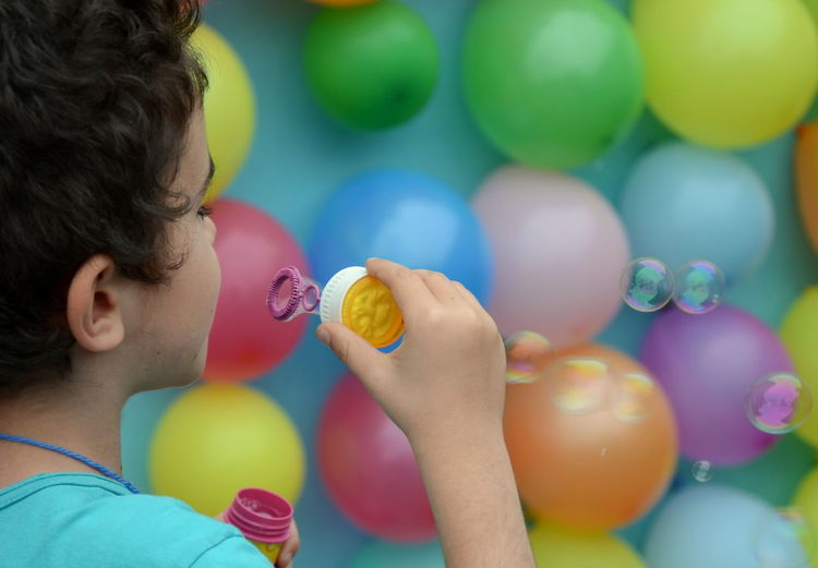 Cropped Image Of Boy Blowing Bubbles Against Multi Colored Balloons