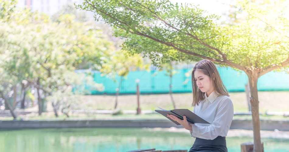 Businesswoman reading file while sitting by lake at park