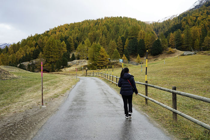 October Travel Photography Zermatt Beauty In Nature Day Full Length Leisure Activity Lifestyles Mountain Nature One Person Outdoors Railing Real People Rear View Road Sky Swizerland The Way Forward Tranquil Scene Tree Walking With Wife Women Young Adult
