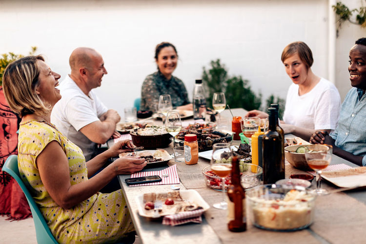Multiracial people sitting at the table having dinner terrace, leisure, food. friends having fun.