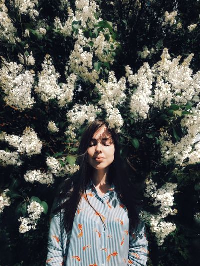 Beautiful Young Woman Standing By Flower Tree
