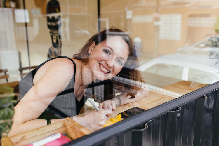 Portrait Of Smiling Woman Seen Through Window