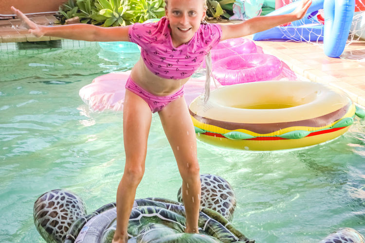 young girl having fun surfing on an inflatable in a swimming pool Water Real People Lifestyles Leisure Activity Women Swimwear Enjoyment One Person Females Child Girls Pool Day Front View Childhood Swimming Pool Happiness Three Quarter Length Outdoors Innocence Inflatable  Vacations Summertime