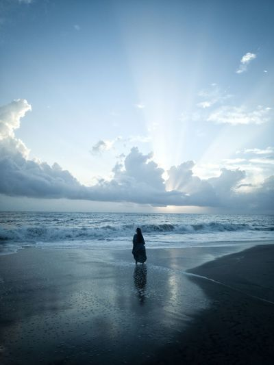 Silhouette woman standing at beach against cloudy sky