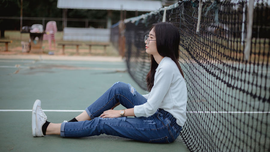 Young woman sitting against tennis net at court