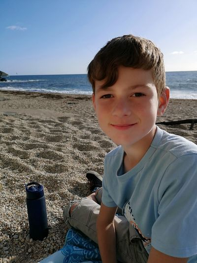 Portrait of boy sitting on shore at beach against sky