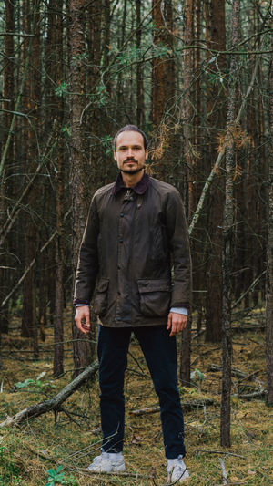 Portrait of man standing against trees in forest